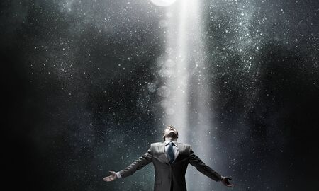 Businessman with hands spread apart standing in light coming from above Stock Photo