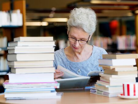 business book: Elderly lady reading books in library Stock Photo