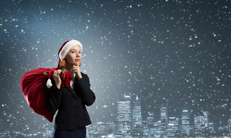 express positivity: Thoughtful Santa woman with red gift bag on back Stock Photo