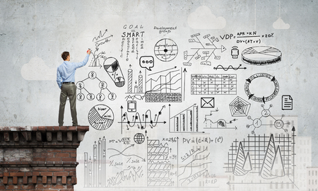 science education: Back view of businessman drawing plan sketches on wall