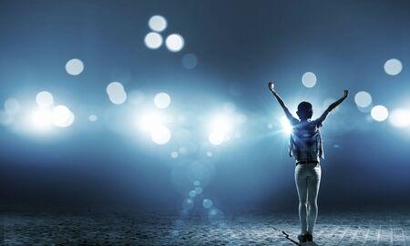 Vue arrière d'une jeune fille avec les mains jusqu'à debout dans les lumières de scène