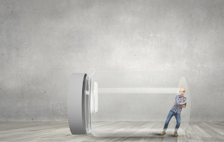trapped: Builder man trapped in glass jar trying to escape Stock Photo