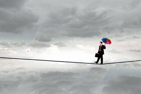 balanza: Hombre de negocios con el paraguas en equilibrio sobre la cuerda de alta en el cielo Foto de archivo