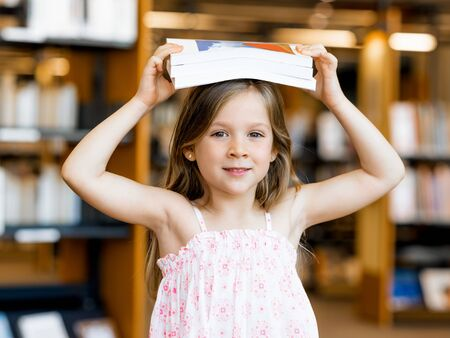 intelligently: Little girl with a book on top of her head in library