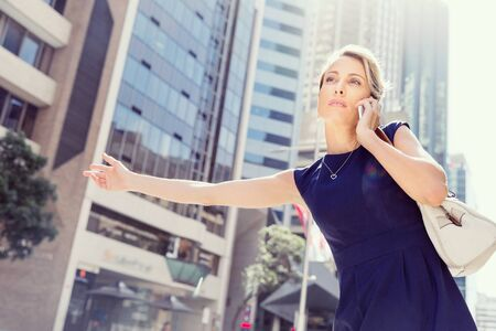 taxi: Businesswoman trying to catch a taxi in business cuty district Stock Photo