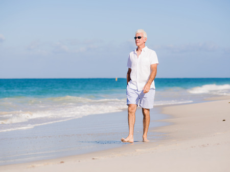 mature men: Man in white clothes on the beach on sunny day