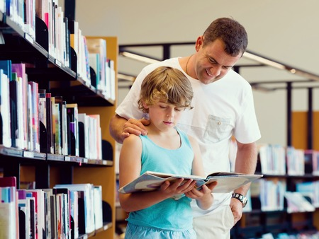 caucasian children: Boy and his father in library choosing books