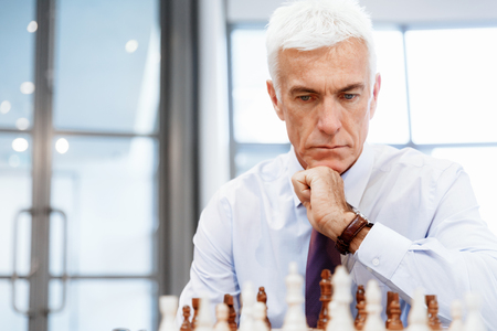 chess men: Businessman in office playing chess