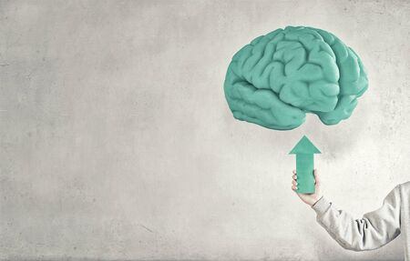 strengthen hand: Close up of hand holding arrow and pointing at human brain Stock Photo
