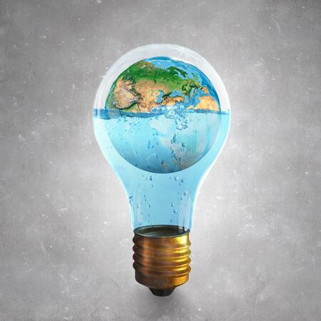 water surface: Glass light bulb and Earth planet inside.  Stock Photo