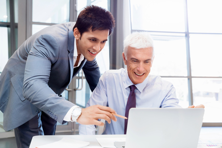 Two businessman in office having discussion in front of computer Stock Photo
