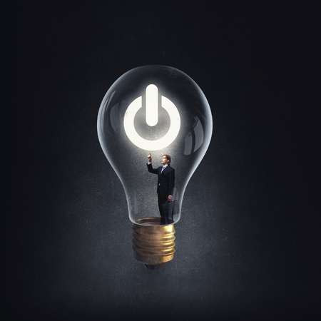 idea: Man holding luminous idea inside light bulb