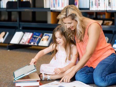 biblioteca: Niñas con sus libros de lectura madre en la biblioteca Foto de archivo