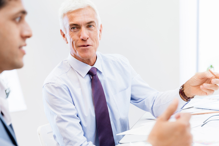 mature business man: Two businessman in office having discussion Stock Photo