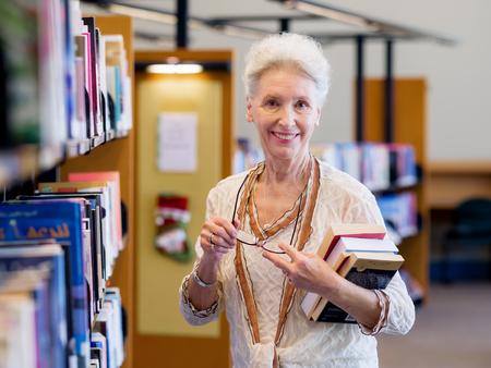 Ältere Dame, die neben Regalen in Bibliothek Buch Standard-Bild