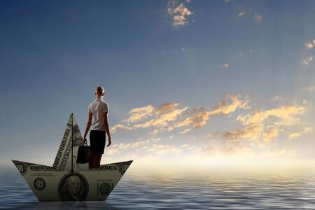escapes: Businesswoman escapes from crisis on paper boat made of dollar banknote Stock Photo