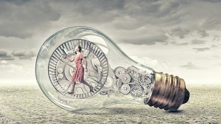 Junge Frau im Kleid mit Buch in den Händen in Glas Glühbirne