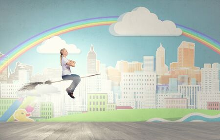 soulfulness: Happy young woman flying in sky on broom