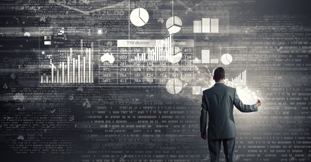 charts graphs: Rear view of businessman drawing marketing charts and graphs Stock Photo