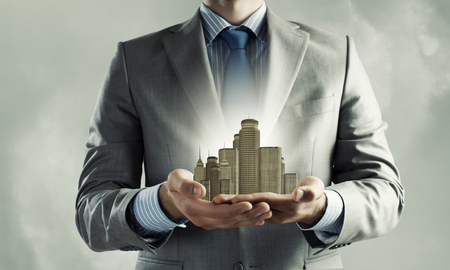 contemporary house: Close up of businessman holding modern office center model in hands