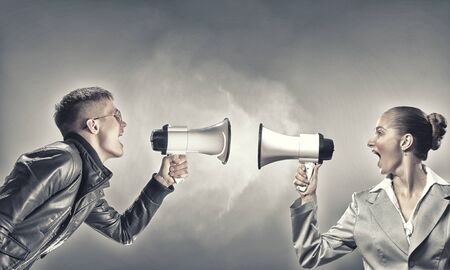 anger management: Furious woman screaming agressively in megaphone at man