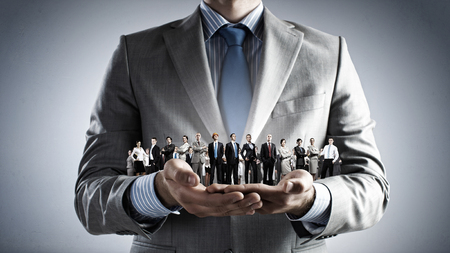 solution: Close up of businessman holding in hands successful people of different professions