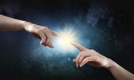mano de dios: Close up de manos humanas que alcanzan el uno al otro con los dedos Foto de archivo