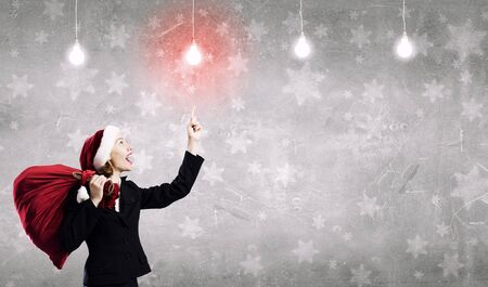 woman hands up: Santa woman with red bag on back pointing on light bulb with finger Stock Photo