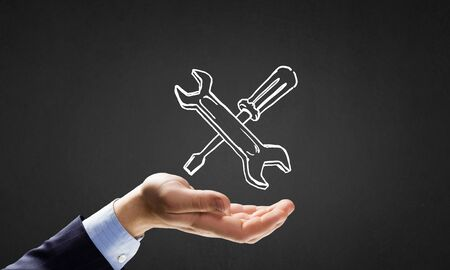 web services: Businessmans hand holding tools over gray background Stock Photo