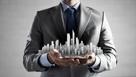 business innovation: Close up of businessman hand holding construction model