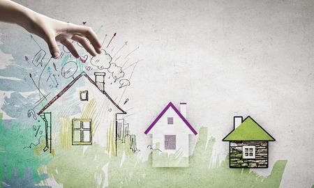 zakelijk: Menselijke hand grijpt getekend op papier huis Stockfoto