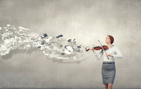 solo violinist: Young pretty businesswoman on cement background playing violin