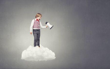 emotionally: Little sweet boy screaming emotionally into megaphone