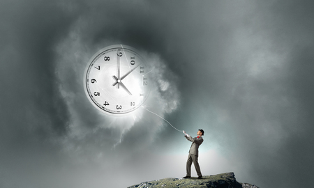 turn back: Young businessman trying to turn back time by pulling clock with rope Stock Photo