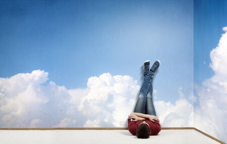 dream body: Young man lying on floor with legs raised up