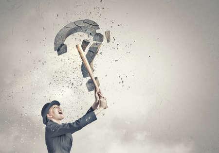emotional woman: Young emotional woman crashing question sign with baseball bat