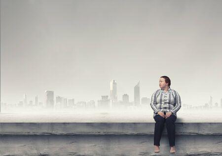 stout: Mujer robusta de mediana edad sentado en la azotea del edificio