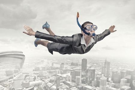 Junge Geschäftsfrau in Anzug und Tauchermaske fliegen im Himmel