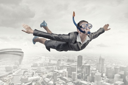 sky dive: Young businesswoman in suit and diving mask flying in sky
