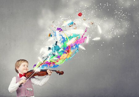 children learning: Adorable boy wearing red bowtie and playing violin Stock Photo