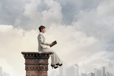 broaden: Adult woman in suit with old book in hand