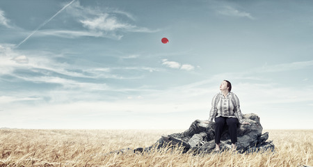 stout: Mujer robusta de mediana edad sentado en la cima de la roca