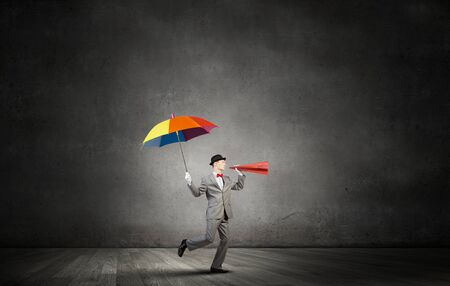 emotionally: Young businessman with colorful umbrella screaming emotionally in paper trumpet