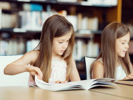 pretty young girl: Little girls reading books in library Stock Photo