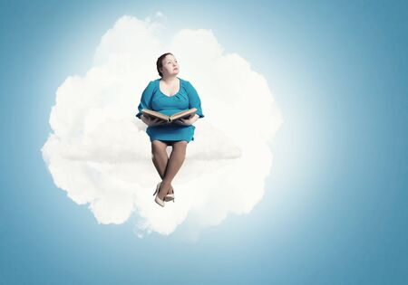 Plus size woman with book in hands sitting on cloud Stok Fotoğraf