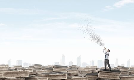 the carefree: Young carefree businessman on pile of old books playing pipe