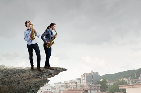 duet: Duet of young man and woman musicians playing saxophones