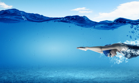 phụ nữ động viên bơi lội trẻ trong mũ và kính dưới nước