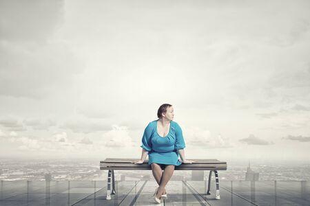 stout: Mujer robusta de mediana edad en el vestido azul sentada en el banco