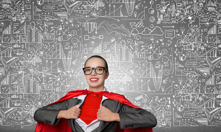 hidden success: Young businesswoman in red cape acting like super hero and sketches on background Stock Photo
